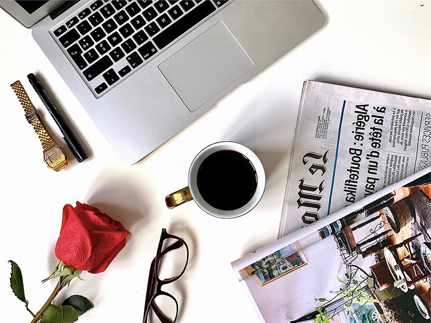 Flatlay magazine ordinateur café lunettes